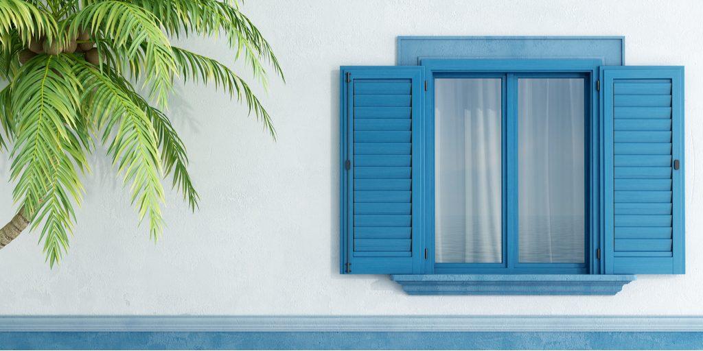 Volet aluminium teinté bleu sur façade maison blanche et palmier